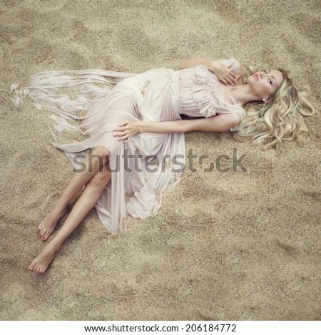Fashion art portrait of beautiful woman on sand - stock photo