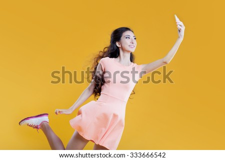Fashion asian young  girl   taking picture of herself, selfie. Portrait on yellow background - stock photo