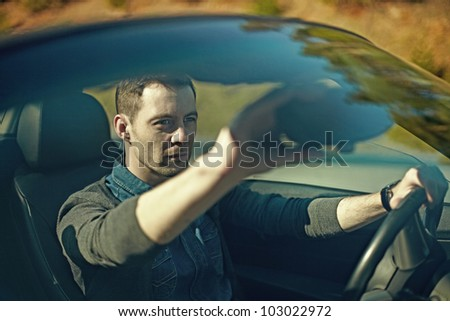 Fashion attractive young man driving his convertible car - stock photo