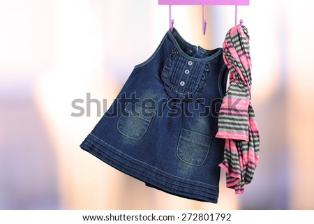 Fashion baby dresses hanging on a hanger on a green  background - stock photo