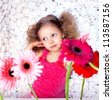 Fashion baby face beautiful child with fair hair in a pink dress holds flowers - stock photo