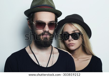 fashion beautiful couple in hat together. Hipster boy and girl. Bearded young man and blonde in sunglasses - stock photo