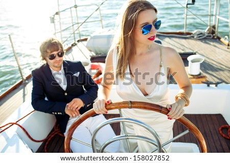 fashion beautiful couple in romantic trip on yacht  - stock photo