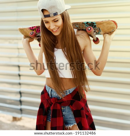 Fashion beautiful girl with skateboard in hand laughing - stock photo