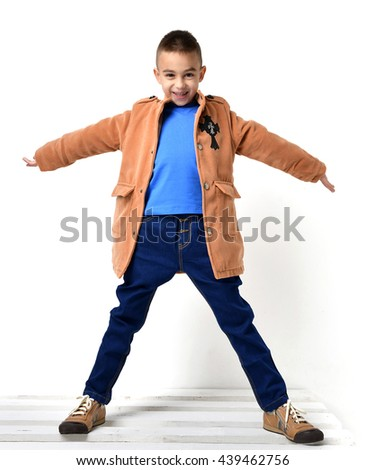 Fashion beautiful little boy in orange brown clothing jacket and jeans standing with spread open hands over white background - stock photo