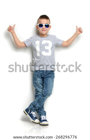 Fashion beautiful little boy in sunglasses t-shirt jeans standing and giving thumbs up sign over white background - stock photo