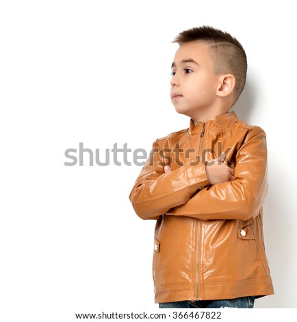 Fashion beautiful little boy in yellow winter brown leather clothing jacket standing and looking at the corner over white background - stock photo