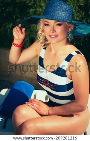 Fashion beautiful woman sunbathing on a chaise lounge near pool outdoors - stock photo