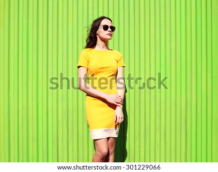 Fashion beautiful young woman in yellow dress and sunglasses against the colorful green background - stock photo