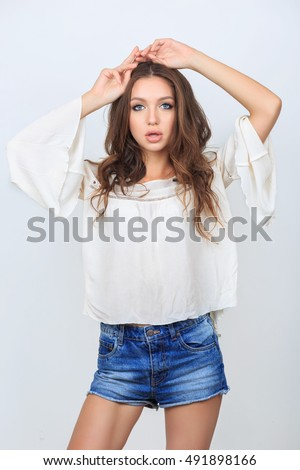 Fashion beautiful young woman model in blue jeans shorts with makeup in studio isolated on white background