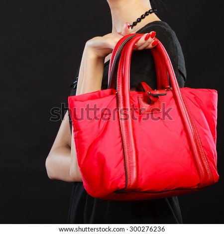Fashion beauty and elegance concept. Elegant lady holding red handbag in hand on black background copy space text area