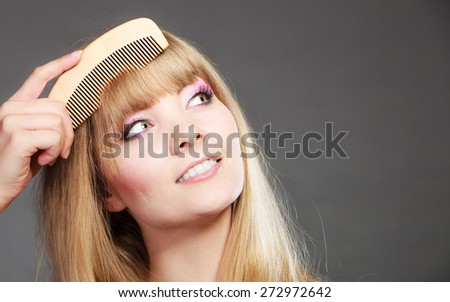 Fashion beauty and haircare concept. Closeup young woman refreshing her hairstyle girl combing her hair fringe with wooden comb - stock photo