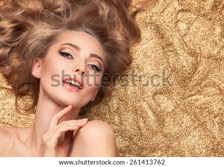Fashion Beauty Girl Lying On Golden Glitter. - stock photo