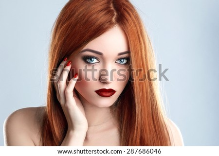 Fashion Beauty Model Woman Long Red Hair. Red Matte Lips and Nails. Blue Eyes. - stock photo