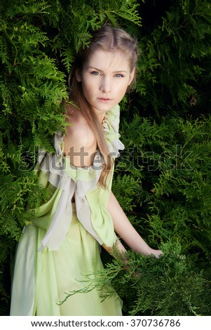 Fashion Beauty Portrait model. Model Woman wearing Long Chiffon dress. Caucasian female blond model outdoors. green fence - stock photo