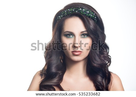 Fashion beauty portrait of a beautiful young brunette woman with make-up on the peacock colors isolated on white background.