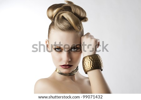 fashion beauty portrait of blond young cute girl with creative hair style and leopard make up, she is in front of the camera, looks in to the lens and has the right hand near the left part of the face - stock photo