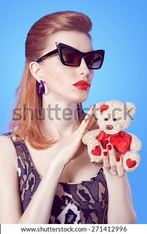 Fashion beauty portrait of Sexy redhead woman in trendy mini dress holds loving teddy bear with red heart on blue. Seductive lady in sunglasses, sensual lips. Provocative girl in playful flirty mood