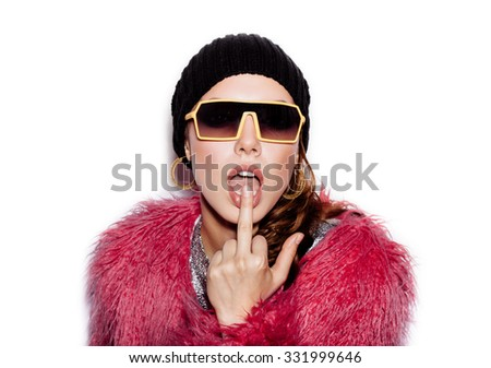 Fashion Beauty Swag Girl wearing sunglasses, pink fur coat, black beanie hat. Stylish Haircut and Makeup. Young Woman licking middle finger on white background no isolated - stock photo