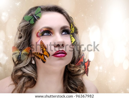 fashion beauty woman with eye make-up and butterfly - stock photo