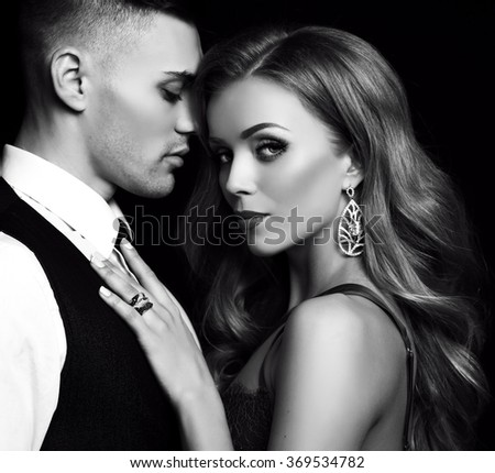 fashion black and studio photo of beautiful couple in elegant clothes, gorgeous woman with long blond hair embracing handsome brunette man