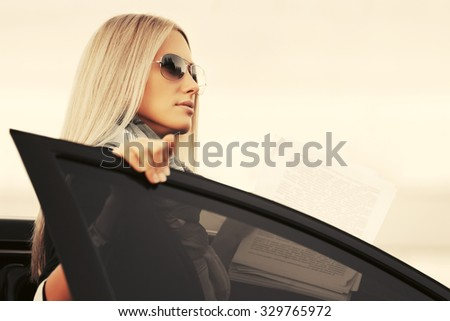 Fashion blond business woman in sunglasses by her car  - stock photo
