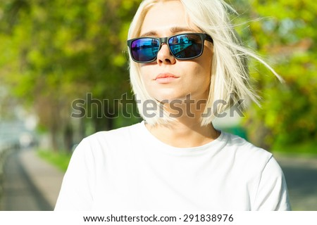 Fashion blond model with sunglasses  in a park in the rays of bright sunshine - stock photo