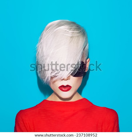 Fashion blond woman with trendy hairstyle and sunglasses on a blue background - stock photo