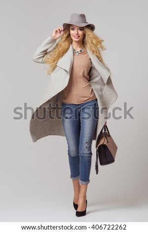 Fashion blonde model in nice clothes posing in the studio. Wearing coat, hat, handbag, ripped jeans