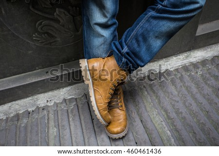 Fashion blue jeans and brown shoes .