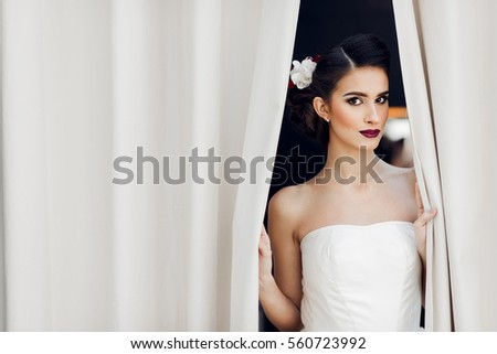 Fashion bride looking through the curtains