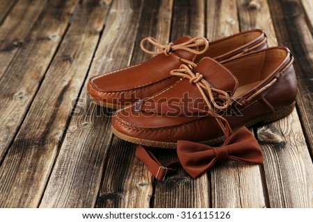 Fashion brown shoes with bow tie on a brown wooden table - stock photo