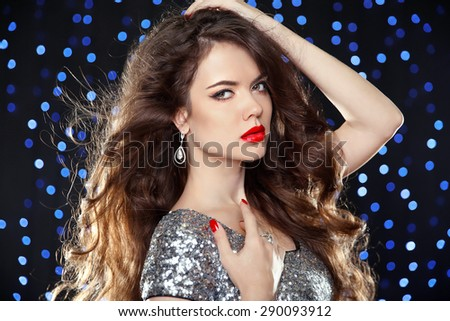 Fashion brunette girl with long wavy hair, beauty makeup, luxury jewelry. Beautiful attractive young woman in dress of sequin posing over holiday lights background. - stock photo