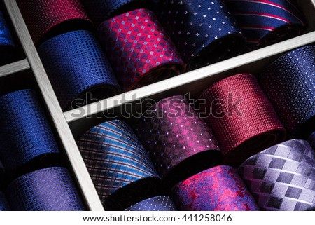 Fashion business background: rolled neckties on display in shop. Photo has copy space