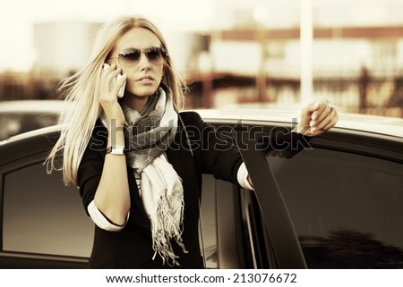 Fashion business woman calling on the cell phone at the car - stock photo