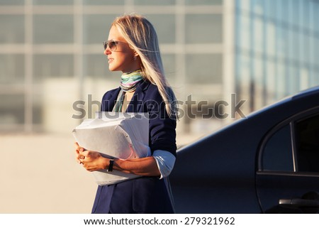 Fashion business woman with financial papers next to her car  - stock photo