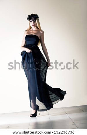 Fashion. Charming Woman in Black Dress and Mask with Feathers walking - stock photo