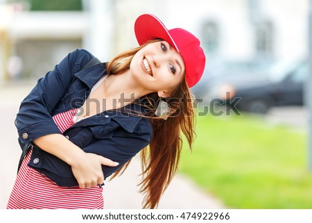 Fashion city portrait of stylish hipster woman, red striped dress, red cap and sneakers, makeup, sunglasses, long brunette hairs, walking alone at weekend, enjoy vacation in Europe, modern trendy