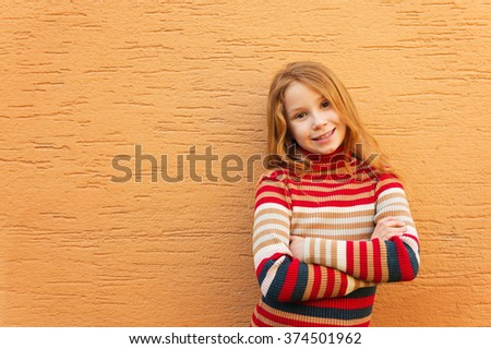 Fashion close up portrait of adorable redheaded girl against orange wall, wearing stripes roll neck pullover - stock photo