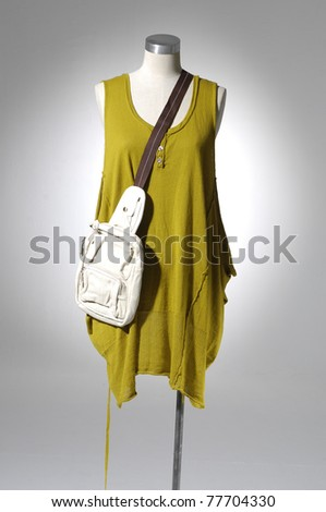 Fashion clothes on a mannequin holding bag in light background - stock photo