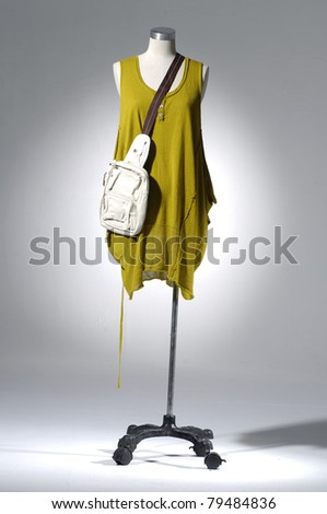 Fashion clothes on a mannequin with bag in light background - stock photo