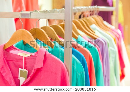 fashion clothing on wooden hangers at the show - stock photo