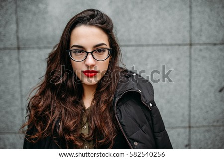Fashion con?ept: bea?tiful young girl with long hair, glasses, red lips standing near modern wall wearing in green suit and grey jeans. Color