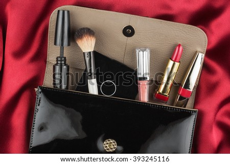 Fashion concept. Black patent leather bag  with cosmetics, on red background - stock photo