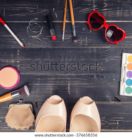 Fashion cosmetic set on a black wooden background background - stock photo