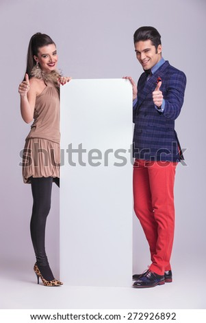 Fashion couple holding a white board while showing the thumbs up gesture. - stock photo