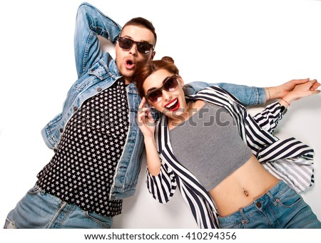 fashion couple in sunglasses lies on a white background, smiling happily and surprised. Vogue Style - stock photo