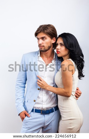 Fashion couple, men wear suit woman sexy dress looking side empty copy space over gray background