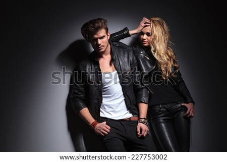 Fashion couple posing on grey studio background, the man si looking at the camera while the woman is leaning on him, looking down. - stock photo