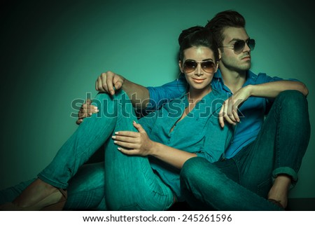 Fashion couple posing on studio background, she is looking at the camera while he is looking away. - stock photo